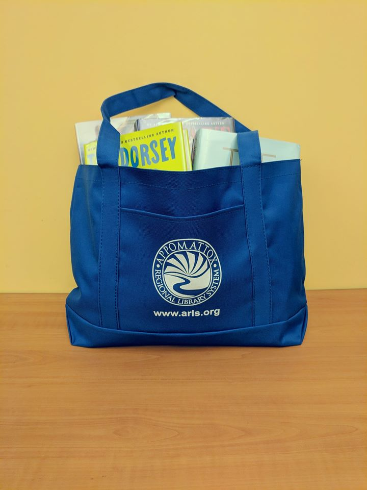 A blue tote bag with the ARLS logo on the front pocket. The bag is full of used books